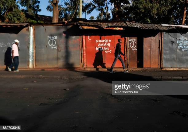 Residents walk past closed shops some with messages calling for peace painted on the doors in the Kibera district of Nairobi on August 16 as life...