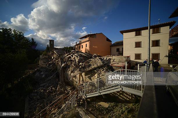 TOPSHOT Residents walk past damaged buildings after a strong earthquake hit Amatrice on August 24 2016 Central Italy was struck by a powerful...