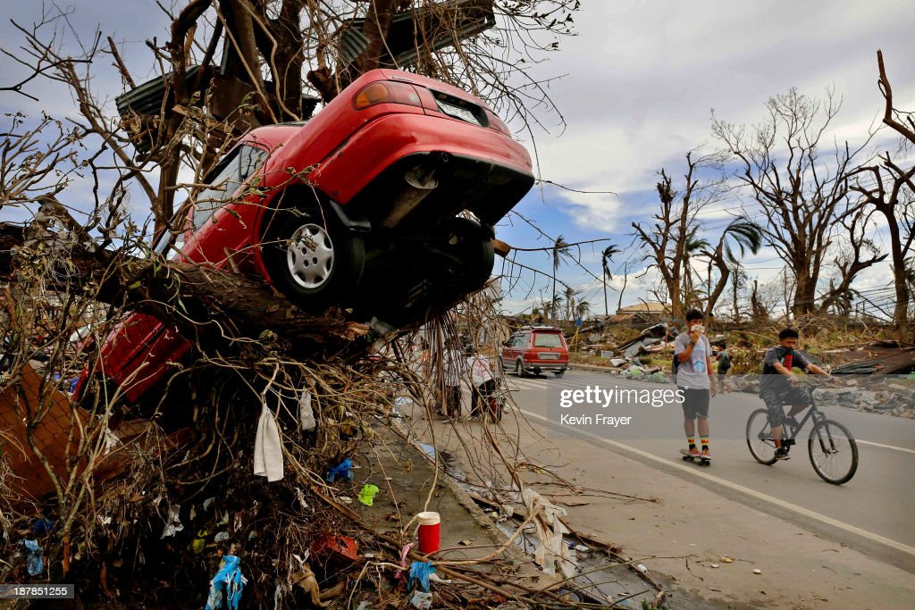 Residents walk past scenes of devastation in the aftermath of Typhoon Haiyan on November 13 2013 in Tacloban Leyte Philippines Typhoon Haiyan packing...