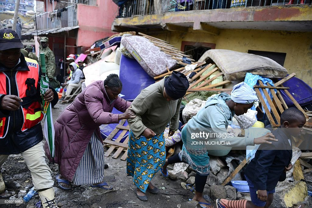 Residents walk past the rubble of a collapsed building in Nairobi as rescue efforts continue on April 30, 2016. Torrential rainstorms in the Kenyan capital have left at least 14 people dead, police said, including at least seven crushed when a six-storey building collapsed, as rescue teams shifted rubble in a desperate search for survivors. / AFP / JOHN