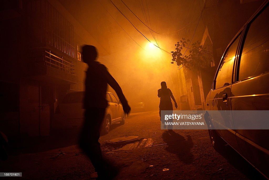 Residents walk through a cloud of smoke after municipal health workers fumigated a neighbourhood against mosquitoes in New Delhi on November 7, 2012. Dengue continued to spread in the Indian capital with 39 fresh cases being reported November 7, taking the toll of people detected with the mosquito-borne disease this season to 1,288, according to Press Trust of India (PTI).