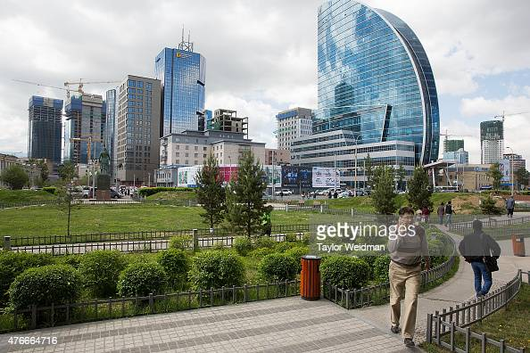 Residents walk through a downtown garden on June 11 2015 in Ulaanbaatar Mongolia A few years ago Mongolia boasted one of the world's fastest growing...