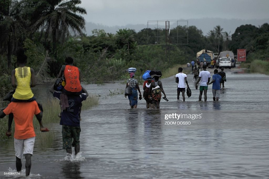 Residents walk through a flooded street in Monrovia on July 1, 2016 following heavy rains. Heavy rains have cut the only road access to Liberia's main airport, leaving travellers to cross some sections by canoe, passengers told AFP on July 1. At certain points the sole road between the capital Monrovia and Roberts International Airport is 1.5 metres (five feet) underwater. DOSSO