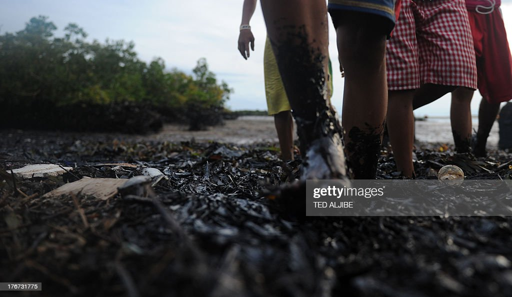 Residents walk through a mangrove area affected by an oil slick near the site of a ferry and freighter collision in Cordova town near Cebu City, central Philippines on August 18, 2013. Philippine divers hauled bodies out of rough seas August 18 in the grisly aftermath of a ferry disaster that claimed at least 38 lives, as oil leaked from the vessel, spreads for more than five kilometres (three miles) and into coastal villages, fishing grounds and mangroves.