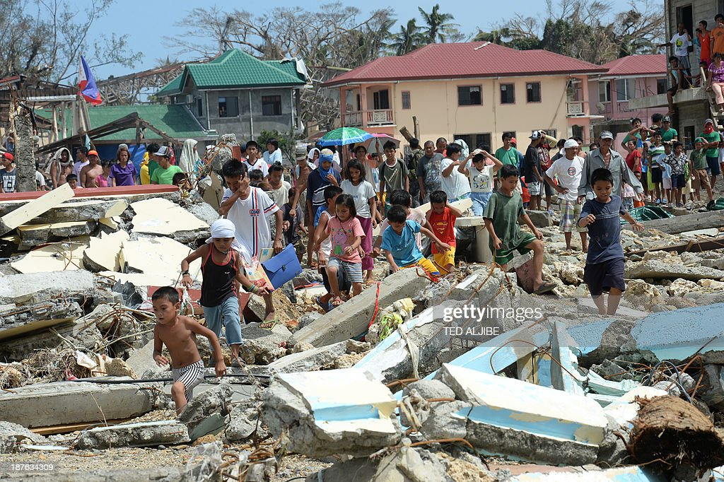Residents walk through debris as they rush to a rescue helicopter delivering relief foods in Hernani town, Eastern Samar province, central Philippines on November 11, 2013, four days after Typhoon Haiyan hit the country. Philippines rescue workers struggled to bring aid to famished and destitute survivors on November 11 after the super typhoon that may have killed more than 10,000 people, in what is feared to be the country's worst natural disaster.