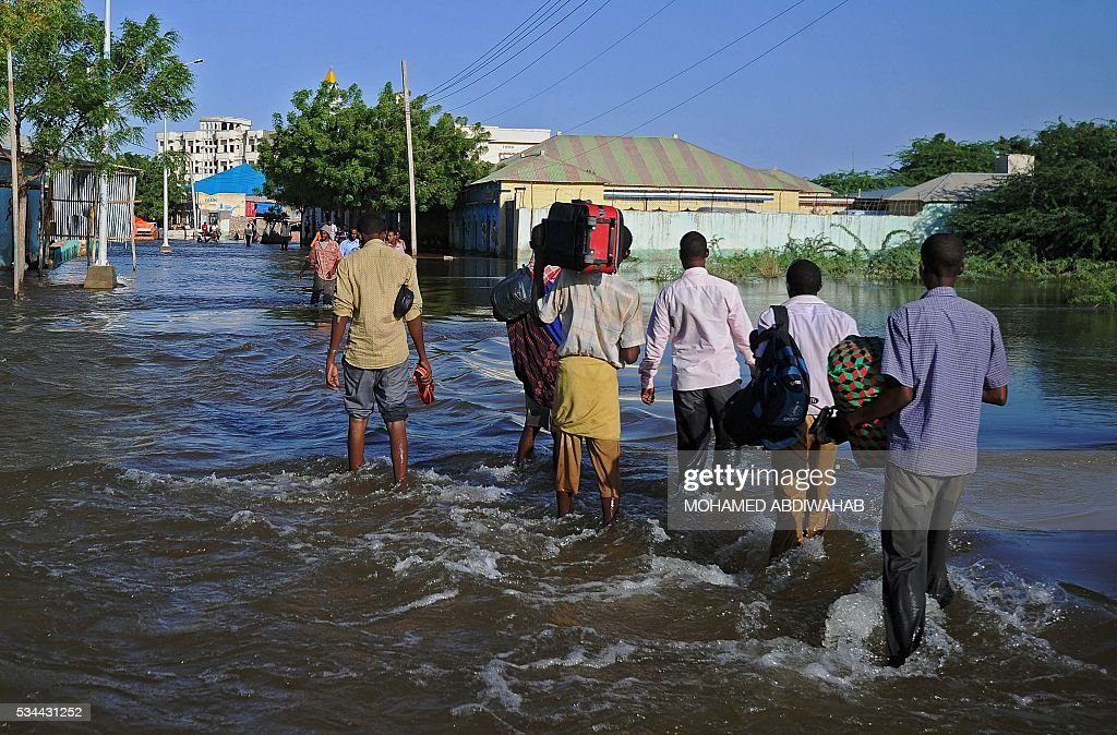 Residents walk through flooded streets in Beledweyne, north of Mogadishu on May 26, 2016. Hundreds of families have been forced out of their homes following flash floods in Beledweyne after torrential rains pounded the area in the last few days.The heavy rains led to the bursting of River Shabelle which caused massive floods in residential areas along the river. / AFP / MOHAMED