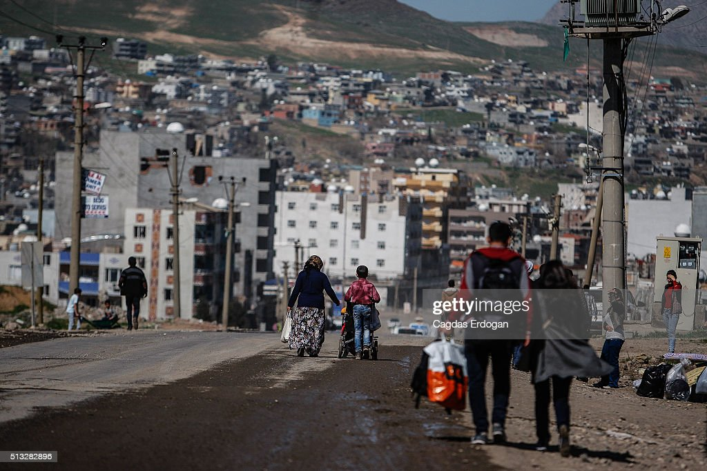 Residents walk with their belongings to southeastern Turkish city of Cizre after the curfew on March 2 2016 in Cizre Turkey Turkish authorities...