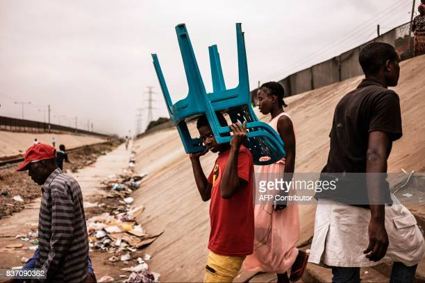 Residents walks across a train track in the Viana district in Luanda on August 22 2017 With current president Dos Santos standing down after the...