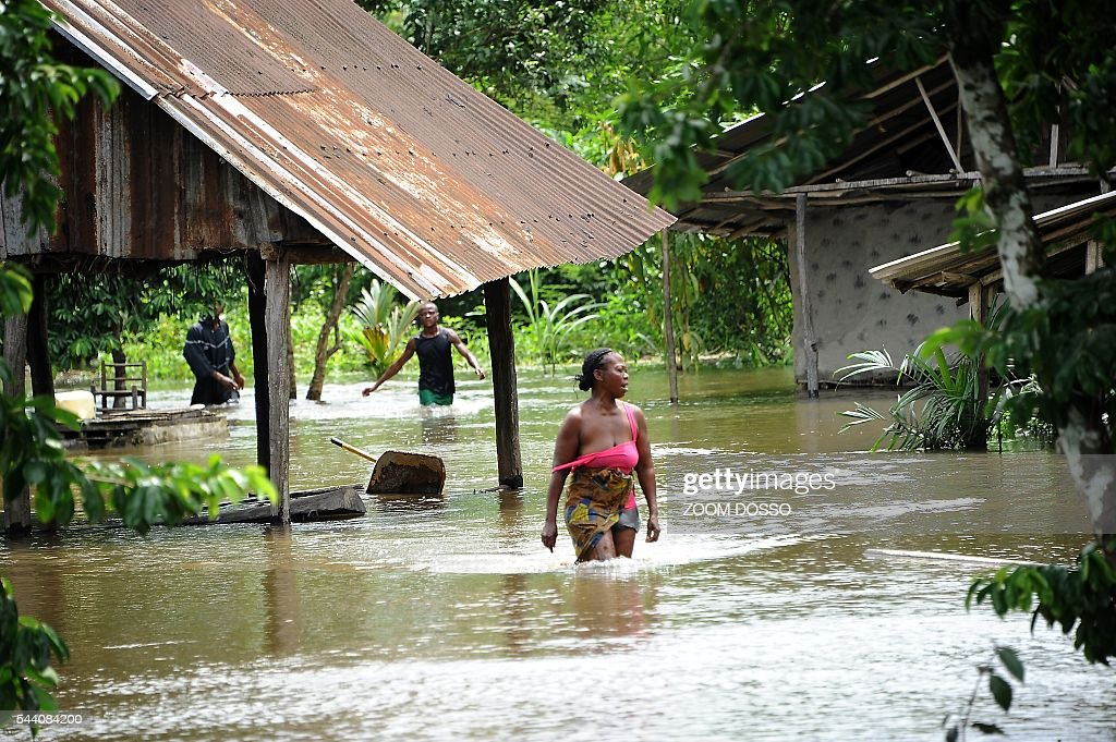 Residents walks through a flooded area in Monrovia on July 1, 2016 after heavy rains. Heavy rains have cut the only road access to Liberia's main airport, leaving travellers to cross some sections by canoe, passengers told AFP on July 1. At certain points the sole road between the capital Monrovia and Roberts International Airport is 1.5 metres (five feet) underwater. DOSSO