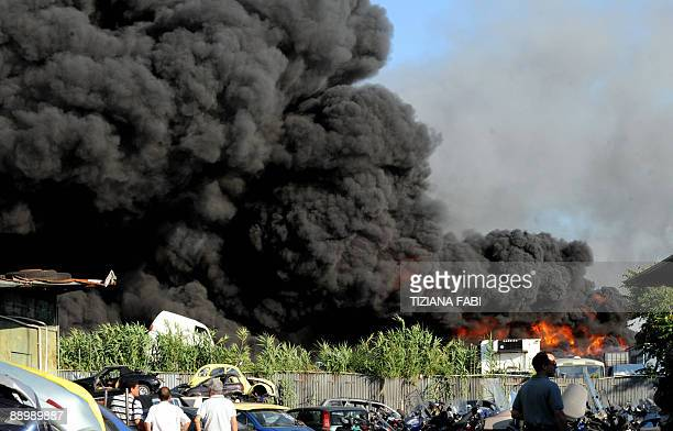 Residents watch a huge blaze breaking in via dell'Almone south of Rome at a warehouse containing around 1000 cars on July 12 2009 AFP PHOTO/ Tiziana...