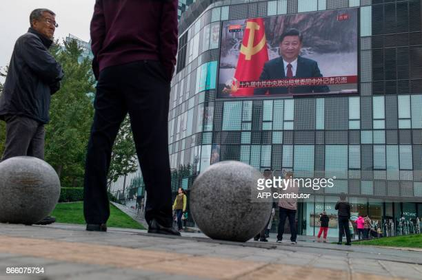 Residents watch a large screen showing Chinese President Xi Jinping attending the Communist Party of China's new Politburo Standing Committee the...