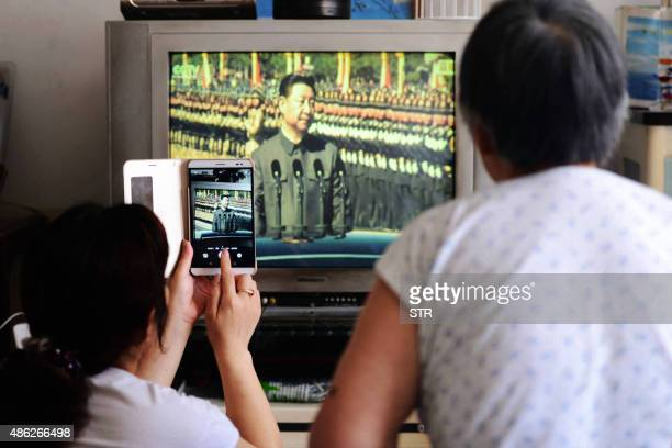 Residents watch a military parade to mark the 70th anniversary of victory over Japan and the end of World War II on television at their home in...