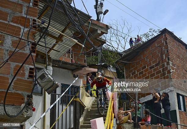 Residents watch as a downhill rider competes during the Adrenalina Urban Bike race final at the Comuna 13 shantytown in Medellin Antioquia department...