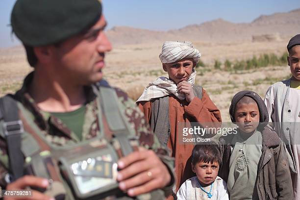 Residents watch as a soldier from the Afghan National Army walks through their village during a joint patrol with the US Army's 4th squadron 2d...