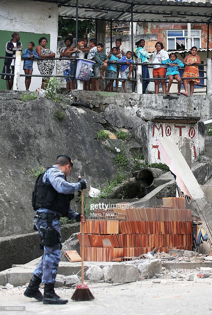 Residents watch as a special forces soldier sweeps up during a 'pacification' operation in the favela complex of Lins de Vasconcelos, in the North Zone, on October 6, 2013 in Rio de Janeiro, Brazil. The favela complex, or shanty town, was previously controlled by drug traffickers and will now be occupied by the city's 35th UPP or 'Police Pacification Unit'. The favela pacifications are occurring amid Rio de Janeiro's efforts to improve security ahead of the 2014 FIFA World Cup and 2016 Olympic Games.