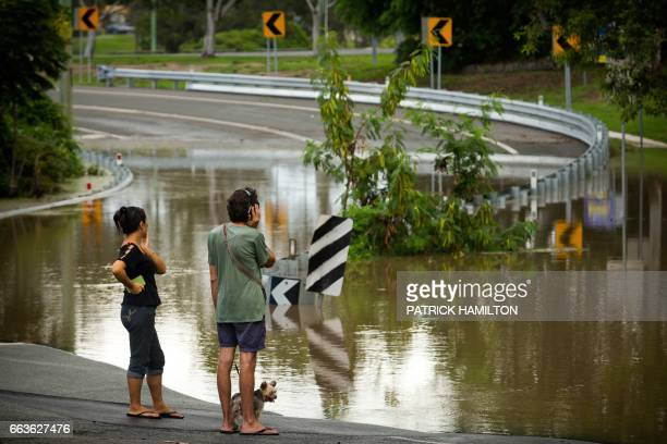 TOPSHOT Residents watch as floodwaters caused by Cyclone Debbie recede in Beenleigh on April 2 2017 Rising floods continued to plague parts of...