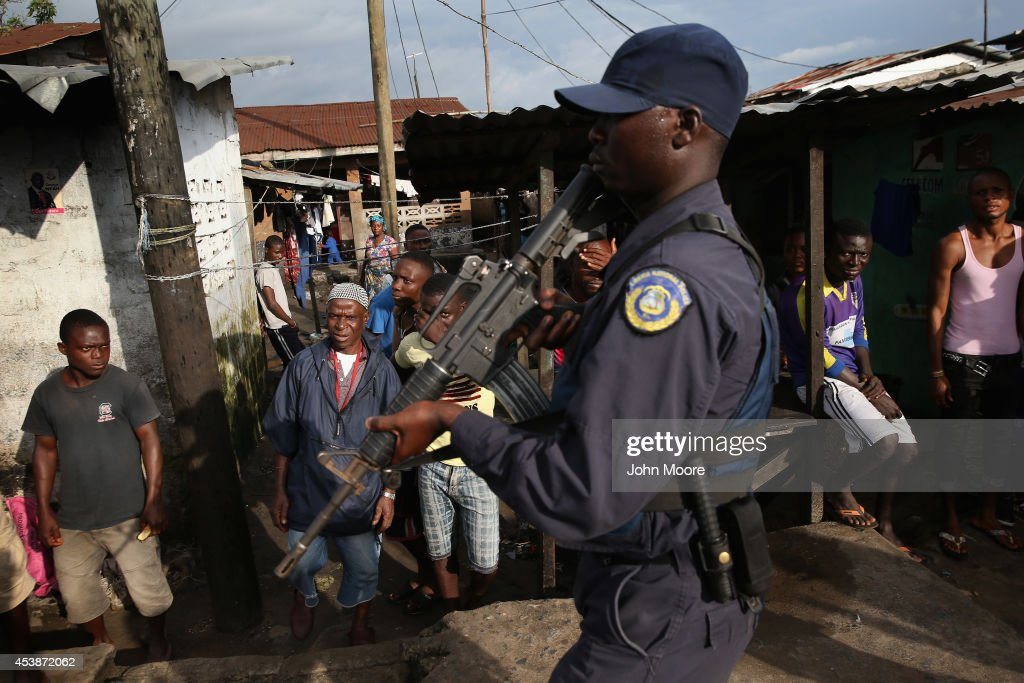 Residents watch as Liberian security forces, part of the country's Ebola Task Force, enforce a quarantine on the West Point slum on August 20, 2014 in Monrovia, Liberia. The quarantine of West Point, a congested favella of 75,000 people, began Wednesday, as the government tries to stop the spread of the virus in the capital city. A mob overran and closed an Ebola isolation ward there on August 16. The Ebola virus has killed more than 1,200 people in four African nations, more in Liberia than any other country.
