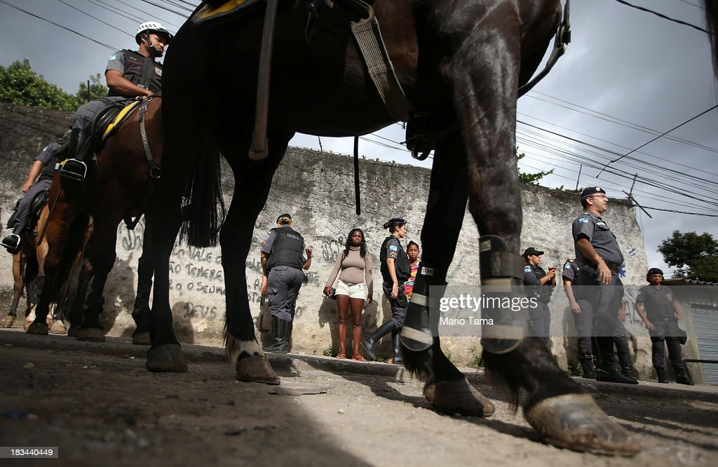 Residents watch as military police on horseback patrol during a 'pacification' operation in the favela complex of Lins de Vasconcelos, in the North Zone, on October 6, 2013 in Rio de Janeiro, Brazil. The favela complex, or shanty town, was previously controlled by drug traffickers and will now be occupied by the city's 35th UPP or 'Police Pacification Unit'. The favela pacifications are occurring amid Rio de Janeiro's efforts to improve security ahead of the 2014 FIFA World Cup and 2016 Olympic Games.