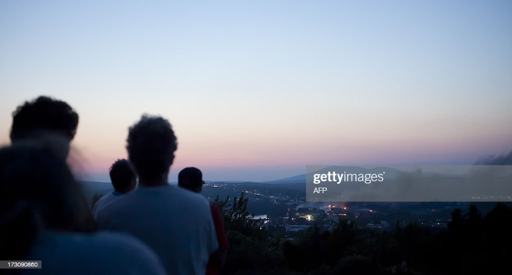 Residents watch from a hill as firefighters douse blazes after a freight train loaded with oil derailed in Lac-Megantic in Canada's Quebec province on July 6, 2013, sparking explosions that engulfed about 30 buildings in fire. At least 80 people are missing after a driverless oil tanker train derailed and exploded in the small Canadian town of Lac-Megantic, destroying dozens of buildings, a firefighter back from the scene told AFP. AFP PHOTO / François Laplante-Delagrave