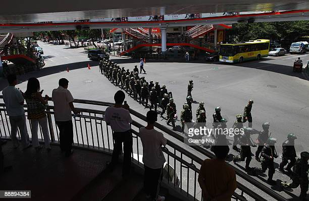 Residents watch policemen as they are deployed to end the ethnic violence between Muslim Uighurs and Han Chinese on July 8 2009 in Urumqi the capital...