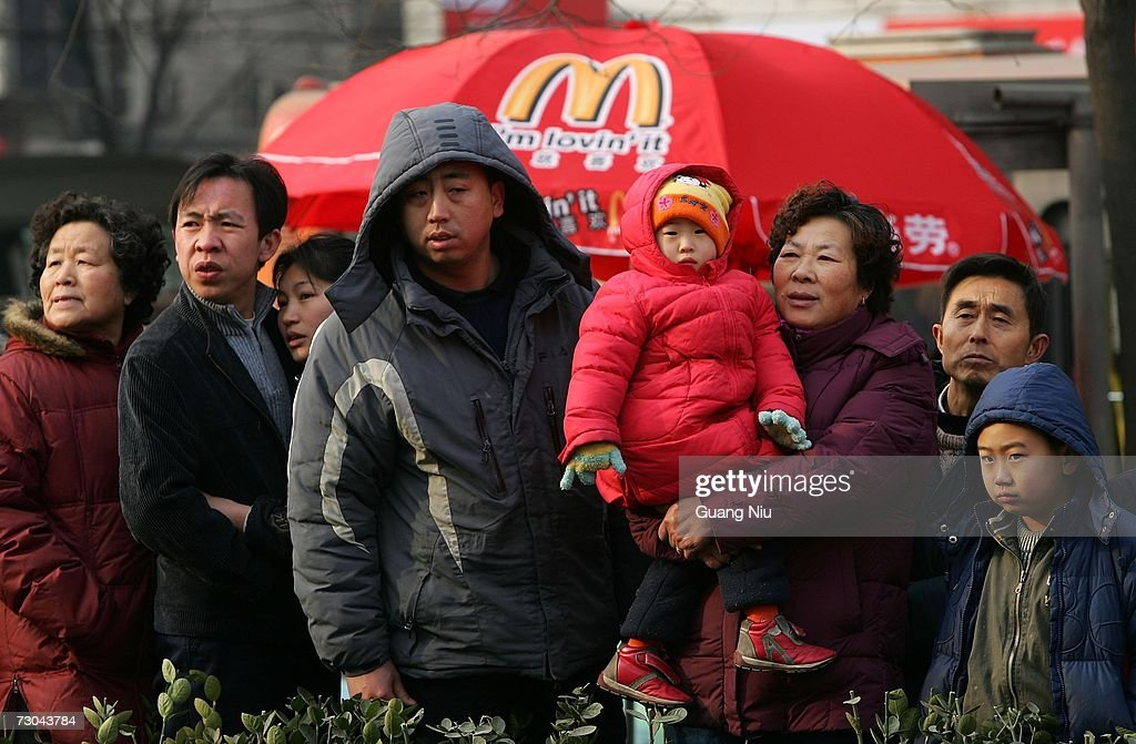Residents watch the opening ceremony for a new McDonald's drive-thru facility on January 19, 2007 in Beijing, China. McDonald's opened its first restaurant in mainland China in 1990, in Shenzhen, Guangdong province and now operates 760 restaurants countrywide, which employ over 50,000 people.