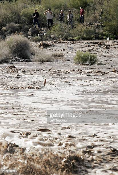 Residents watch the rushing Agua Fria River on Squaw Valley Road December 29 2004 in Black Canyon City Arizona 50 miles north of Phoenix Heavy rains...