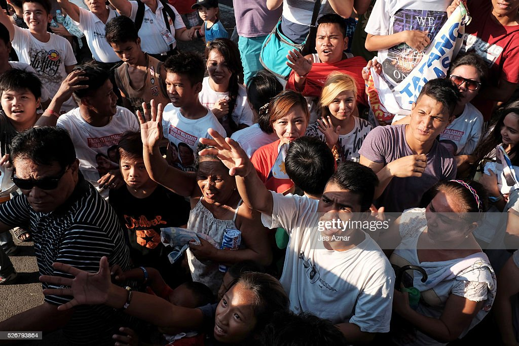 Residents waves and run to catch up with presidential candidate Rodrigo Duterte during a campaign sortie on May 1, 2016 in Manila, Philippines. Presidential Candidate Rodrigo Duterte, a tough-talking mayor of Davao in Mindanao has been the surprise pre-election poll favourite, pulling away from his rivals despite controversial speeches and little national government experience. Opinion polls have shown Mr Duterte has maintained his lead with 33 percent support in the Philippines as Senator Grace Poe looks at an impossible odd, with only 22 percent supporting her. The Philippine presidential campaign ends on May 7 with elections on May 9 and features 5 presidential candidates vying for the top post.
