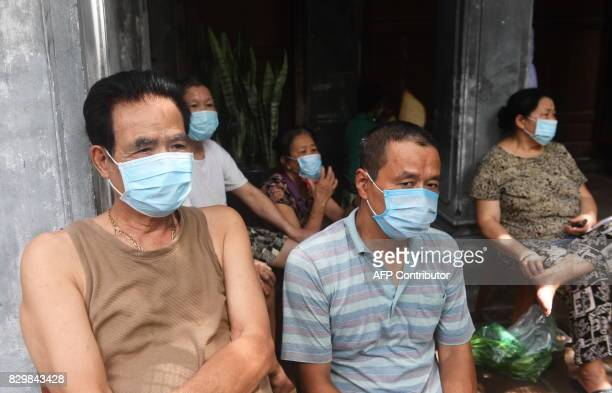 Residents wear masks and wait outside while municipal workers spray chemicals to kill mosquitos inside residential homes in downtown Hanoi on August...