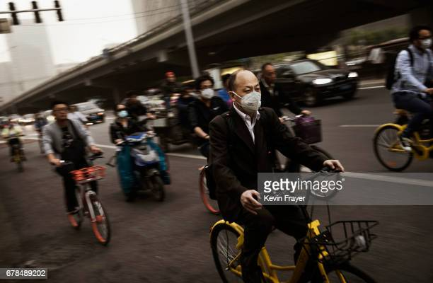Residents wear masks to protect from particles blown in during a sandstorm as they commute on May 4 2017 in Beijing China Sandstorms are common in...