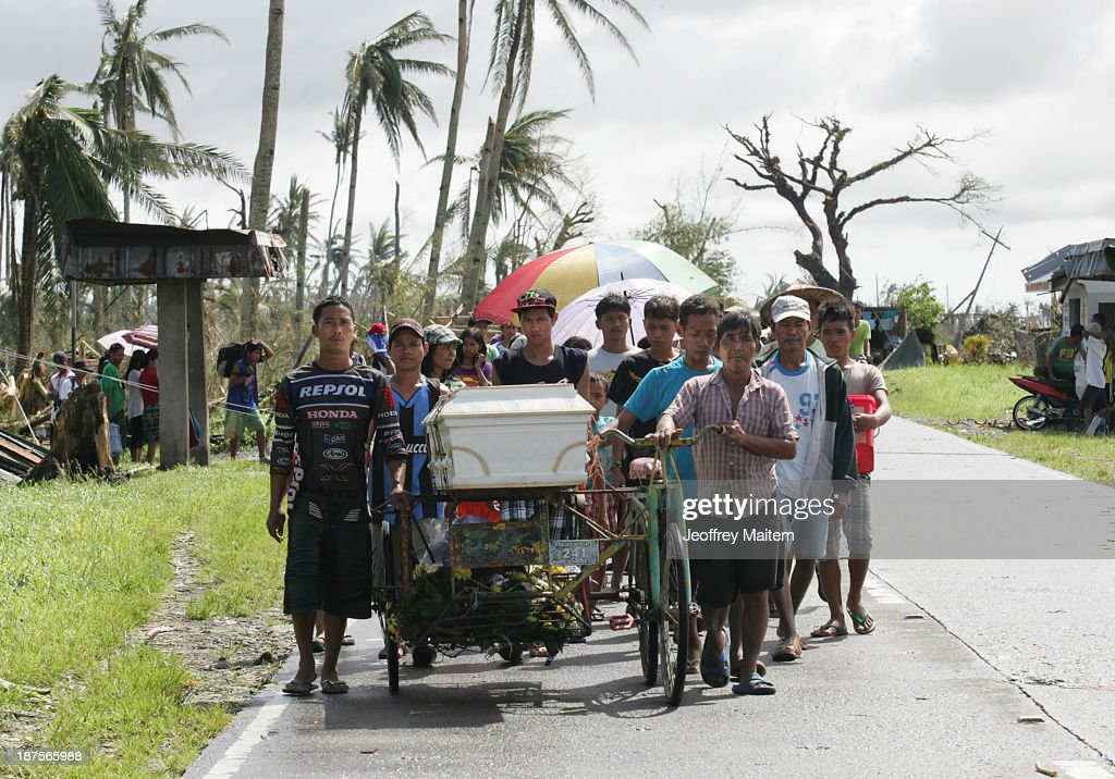 Residents wheel a family member to the cemetery on November 10, 2013 in Santa Fe, Leyte, Philippines. Typhoon Haiyan, packing maximum sustained winds of 195 mph (315 kph), slammed into the southern Philippines and left a trail of destruction in multiple provinces, forcing hundreds of thousands to evacuate and making travel by air and land to hard-hit provinces difficult. Around 10,000 people are feared dead in the strongest typhoon to hit the Philippines this year.