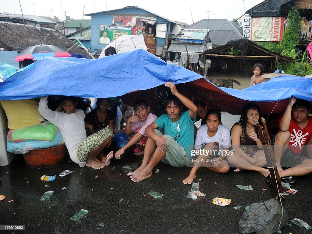 Residents with their belongings rest at a makeshift shelter along a road in Cavite, southwest of Manila on August 19, 2013 after their houses (back) were submerged by flood waters due to heavy rains exacerbated by Tropical Storm Trami. Torrential rain paralysed large parts of the Philippine capital August 19, as neck-deep water swept through homes, while floods in northern farming areas claimed at least one life.