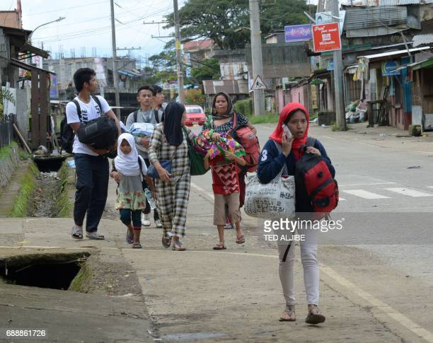 Residents with their belongings walk along a deserted street as they evacuate from their homes in Marawi in southern island of Mindanao on May 27 The...