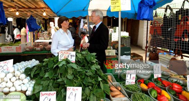 Resigned Conservative MP David Davis with Janet Devers on her fruit and vegetable stall on Ridley Road Market in Hackney east London