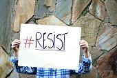 Boy holding resist sign