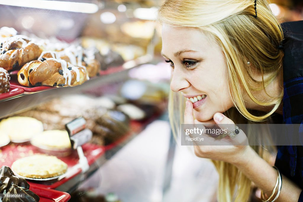 Resistance is futile! Blonde shopper checks cake display in bakery
