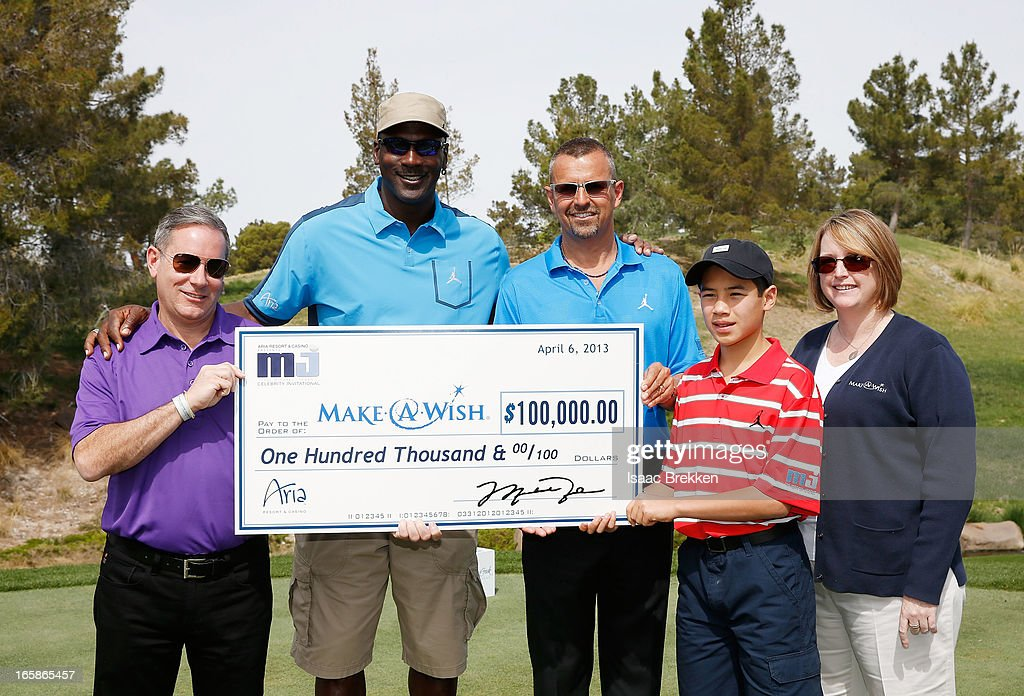 Resort & Casino Vice President of Marketing Carl Cohen, (L-R) NBA legend Michael Jordan, President and Chief Executive Officer of Casino Marketing MGM Resorts International, Anton Nikodemus, Wish Child Joseph Domingues Jr. and Make-A-Wish Vice President of Corporate Alliances, Kathy Forshey pose with a check for $100,000 USD to Make-A-Wish during ARIA Resort & Casino's Michael Jordan Celebrity Invitational golf tournament at Shadow Creek on April 6, 2013 in North Las Vegas, Nevada.