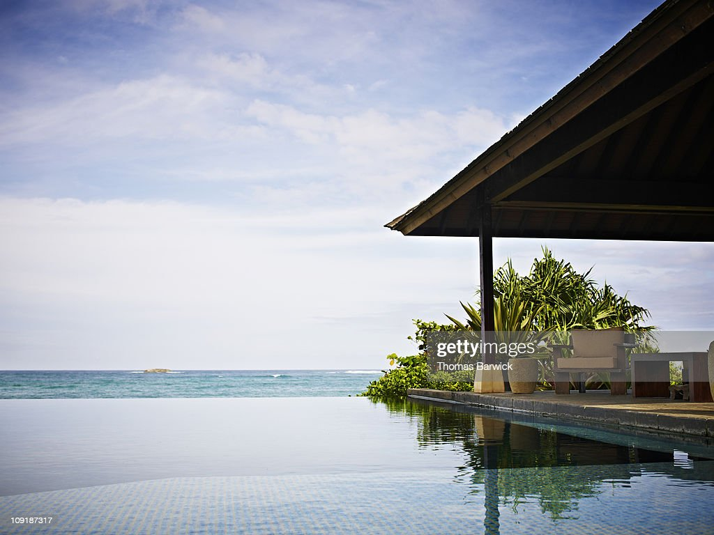 Resort infinity pool and cabana overlooking ocean : Stock Photo