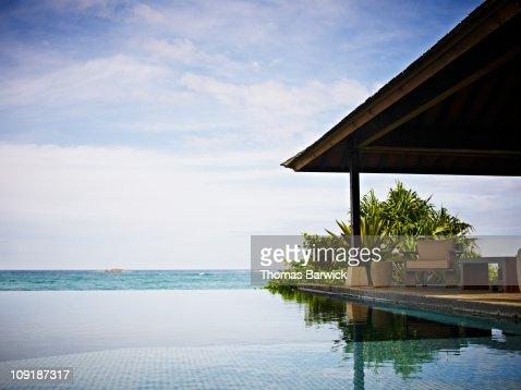 Resort infinity pool and cabana overlooking ocean : Foto de stock