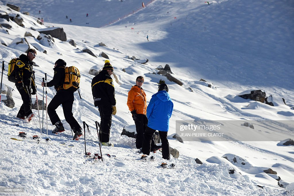 Resort officials stand on December 31, 2013 in the French Alps ski resort of Meribel by the rocky part between two slopes where German retired Formula One legend Michael Schumacher had an accident on December 29. Schumacher's condition has shown a slight improvement after a second operation following his weekend ski accident but he is not out of danger and being kept in a medically-induced coma, doctors said today. AFP PHOTO / Jean Pierre Clatot