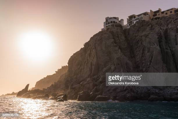Resort vacation houses and villas nested in the rock formations around the Arch in Cabo San Lucas, Mexico at sunset.