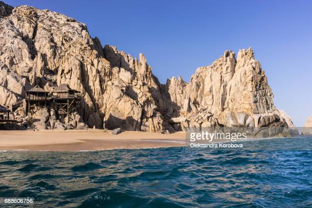 Resort vacation huts and houses nested in the rock formations around the Arch in Cabo San Lucas, Mexico at sunset.