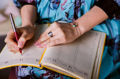 respectable woman is writing notes and planning schedule.  closeup beautiful hand writing notes