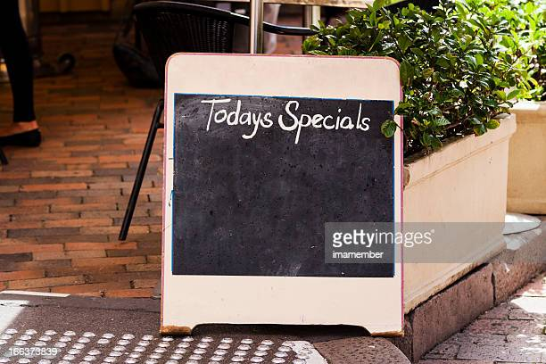Restaurant blackboard sign 'Todays Specials' on footpath, copy space