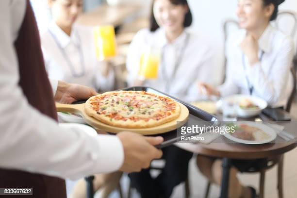 restaurant clerk bringing pizza