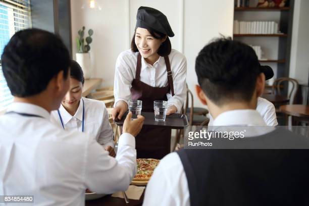 restaurant clerk serving customers with a smiling face
