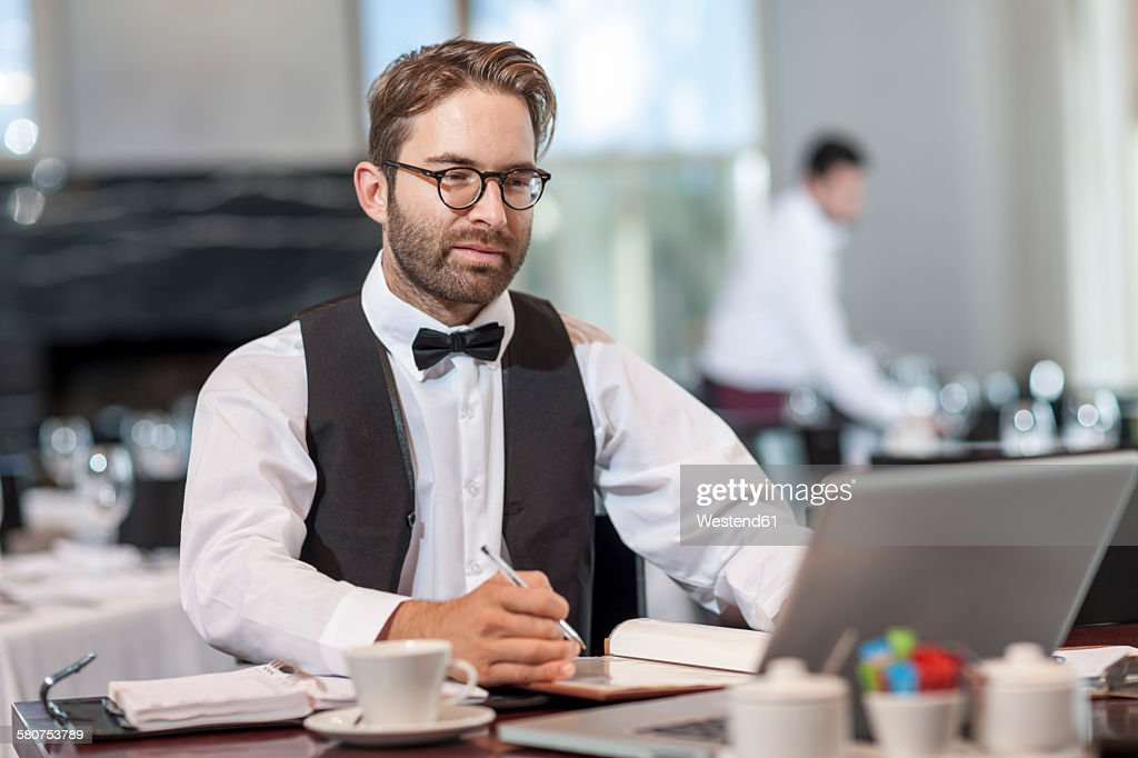 Restaurant employee sitting at table using laptop