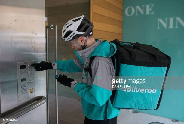 Restaurant Food Delivery company 'Deliveroo' employee Billy Shannon rings a customer's bell while at work in Camden Town north London in November 17...