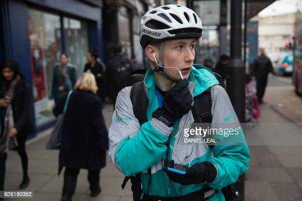 Restaurant Food Delivery company 'Deliveroo' employee Billy Shannon speaks with a customer while working in Camden Town north London in November 17...