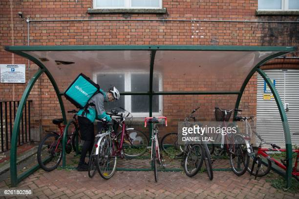 Restaurant Food Delivery company 'Deliveroo' employee Billy Shannon locks his bike while working in Camden Town north London in November 17 2016...