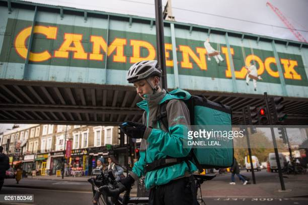 Restaurant Food Delivery company 'Deliveroo' employee Billy Shannon looks for an address while working in Camden Town north London in November 17...